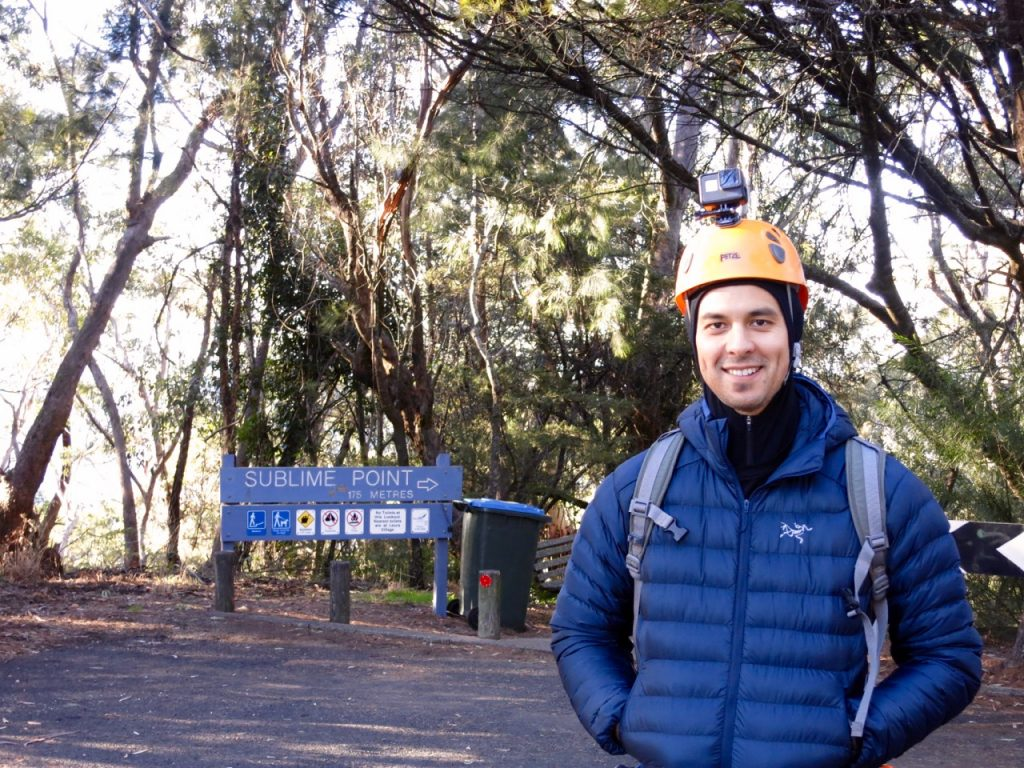 Man standing in jacket next to Sublime Point sign.