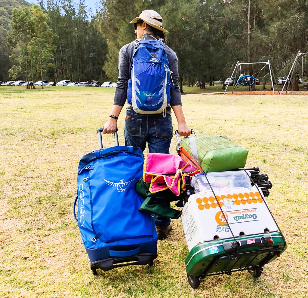 Man wheeling trolleys and bag in campground